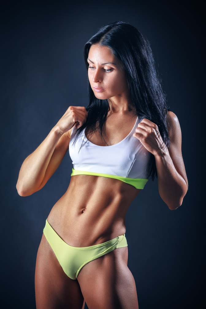 Muscular young woman athlete portrait over dark background