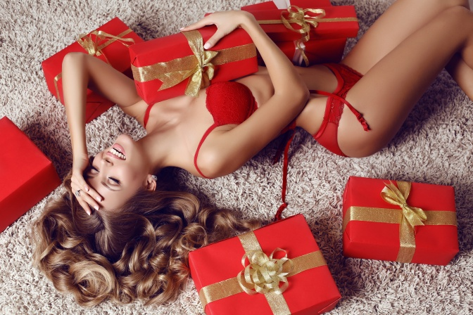 sexy beautiful woman with blond curly hair in lingerie with presents