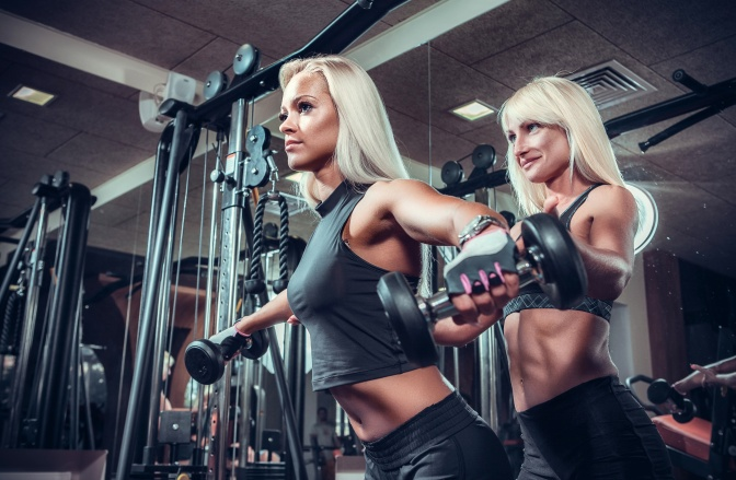 fitness women doing exercises with dumbbell in the gym