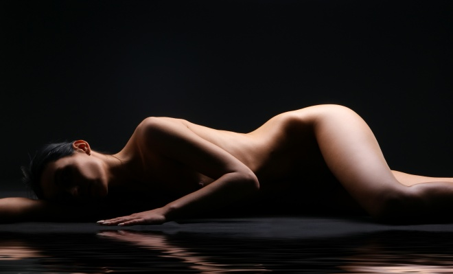 Beautiful naked body of a young Caucasian woman on black