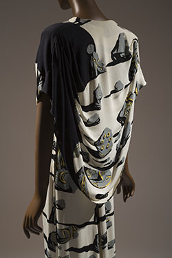 Long evening dress in ivory rayon crinkle crepe printed with surrealist design of gray shattered monument stones with black shadows and yellow ancient inscriptions of keys, insects, eyes, timepieces, words, arrows, birds; deep-V suplice bodice with cap sleeves, asymmetrical black draped capelet, flared train