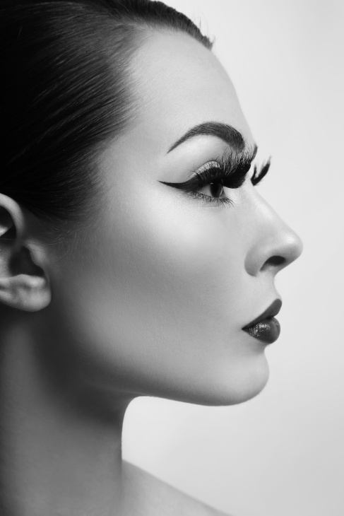 Black and white profile portrait of young beautiful woman with stylish eyeliner