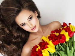 Beauitful young woman with bouquet  of flowers. Attractive girl with long brown curly hair