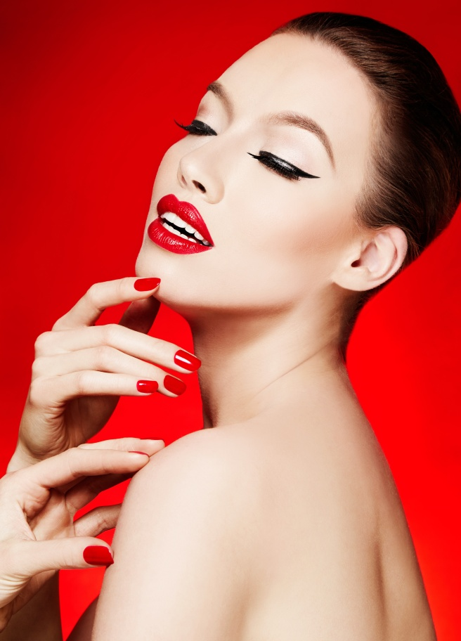 Beauty cosmetic image. Red lipstick and manicured nails isolated on red background.
