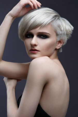 Fashion beauty portrait of a blonde girl with a stylish short haircut on a gray background.