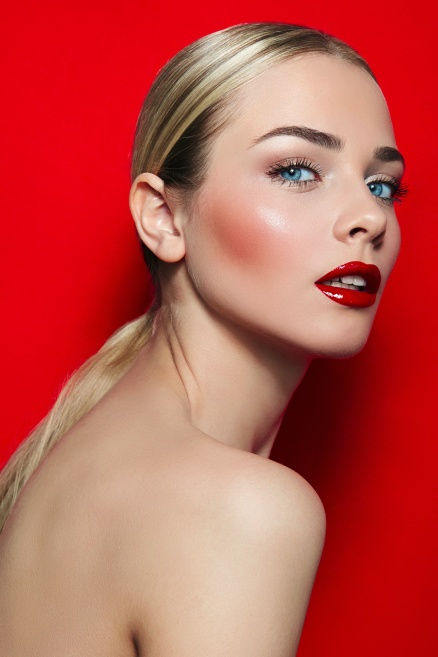 Young beautiful girl on red background in studio. Blue eyes, black eyelashes, red lips, white teeth. Well-groomed, luxurious. Hairstyle - tail, blonde, smooth skin. Beauty salon, fashion, dvertising.