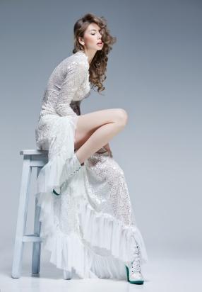 beautiful woman in long white dress posing fashion in the studio